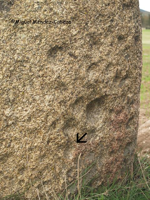 Detalle del menhir mostrando sus cazoletas en término de Talavera de la Reina (Gamonal) y señalado uno de sus canales por la flecha