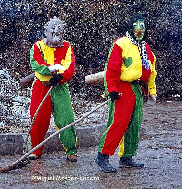 """Dos morraches vestidos con su peculiar indumentaria armados de sus """"porras"""" y con los cencerros colgados a la espalda"""