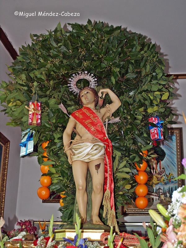 Imagen de San Sebastián preparada para la procesión con un árbol repleto de follaje, naranjas, regalos y panes
