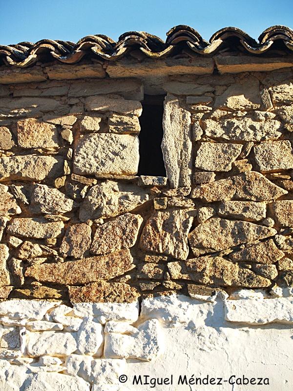 Muro de mampostería granítica en parte encalada con ventanuco de aireación del doblado.