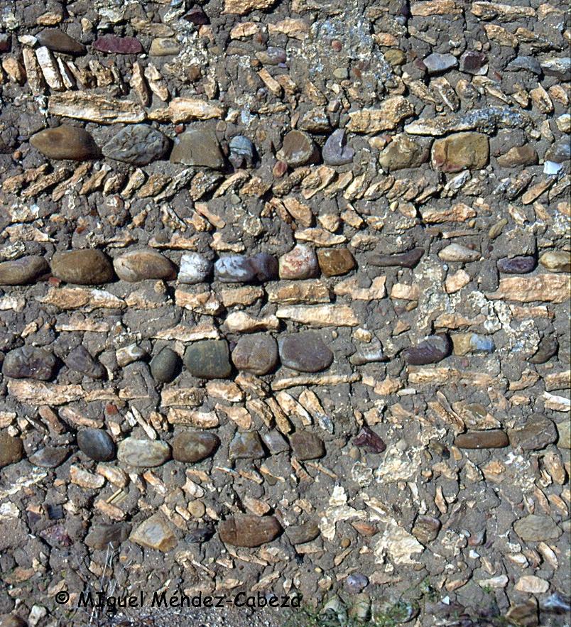 Lentejjones calizos combinados con canto rodado en un muro de Pueblanueva.