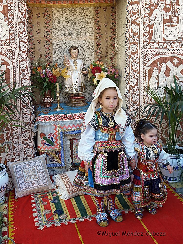 Niños vestidos de lagarterano delante de un altar del Corpus