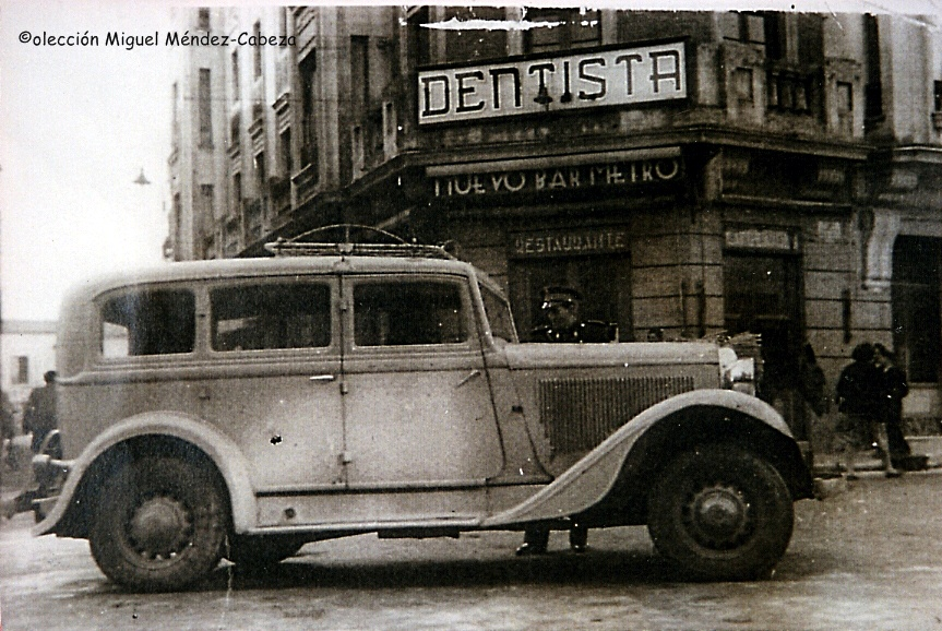 Un guardia detiene a un vehículo en los años cincuenta en la Plaza del Reloj. detrás aparece el bar Metro nuevo y la consulta de Tuñón el dentista