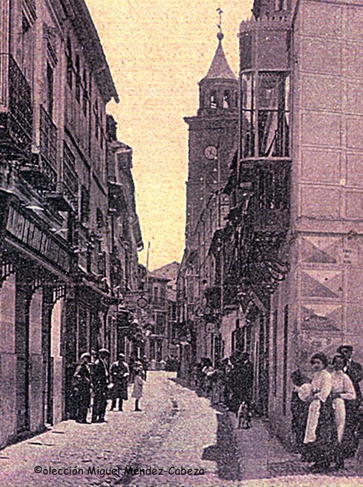 Detalle de la calle Medellín con la antigua torre del reloj al fondo y los tradicionales albañales surcando el centro de la vía
