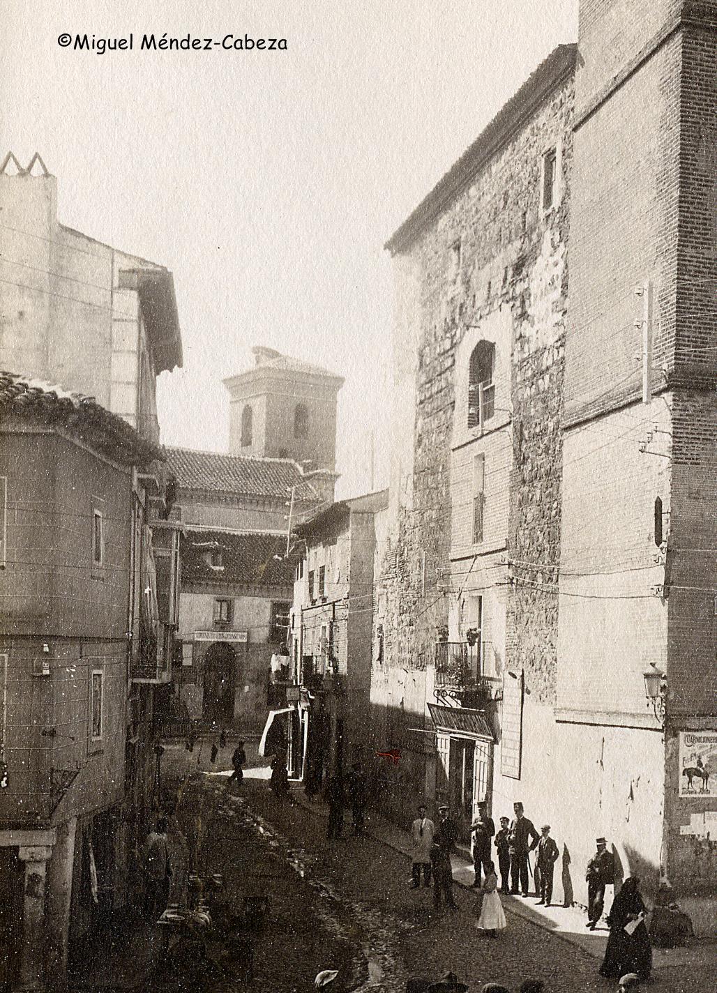 Detalle de una fotografía de Ruiz de Luna con la puerta ya derribada. Al fondo se ve la iglesia de san Pedro que da nombre al arco y a la derecha en primer plano la primitiva torre del reloj y detras una torre albarrana pegada a la antigua puerta de la muralla pero relleno el vano de construcciones posteriores