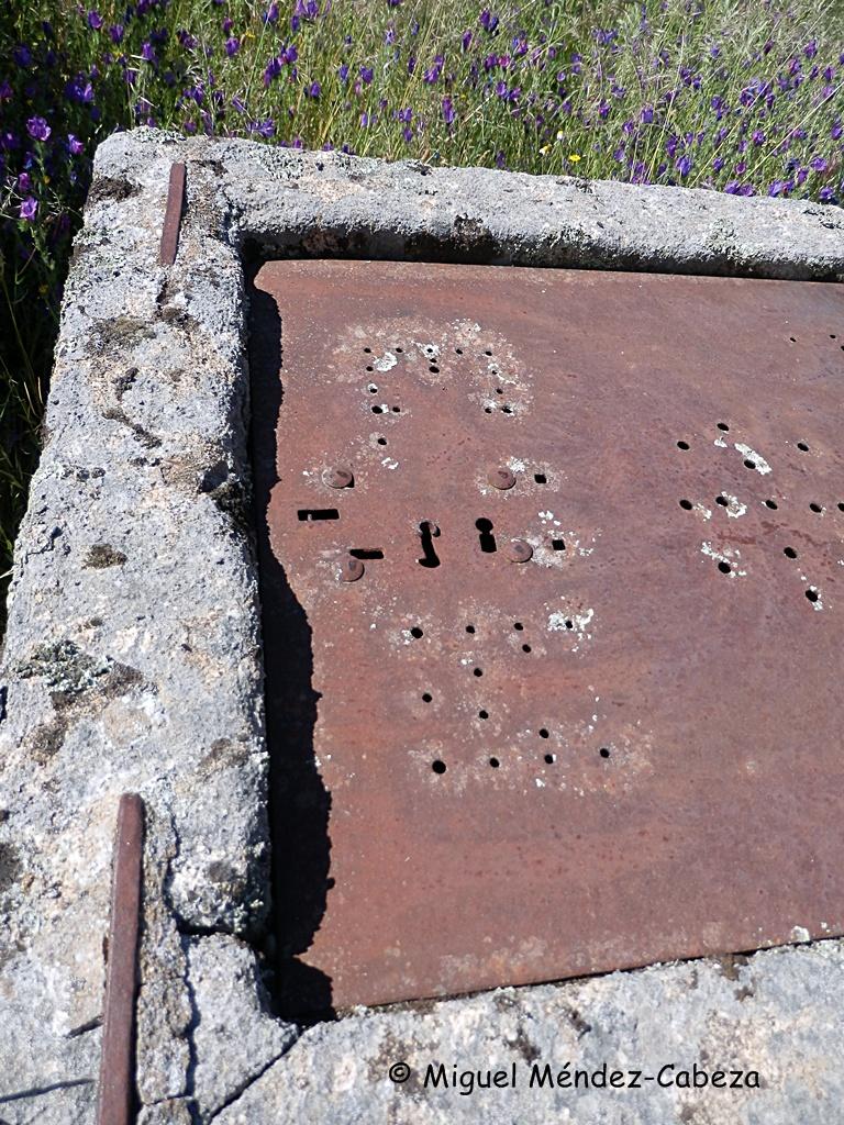 Iniciales del dueño y cerraduras sobre la tapa metálica de un pozo de Valdeverdeja