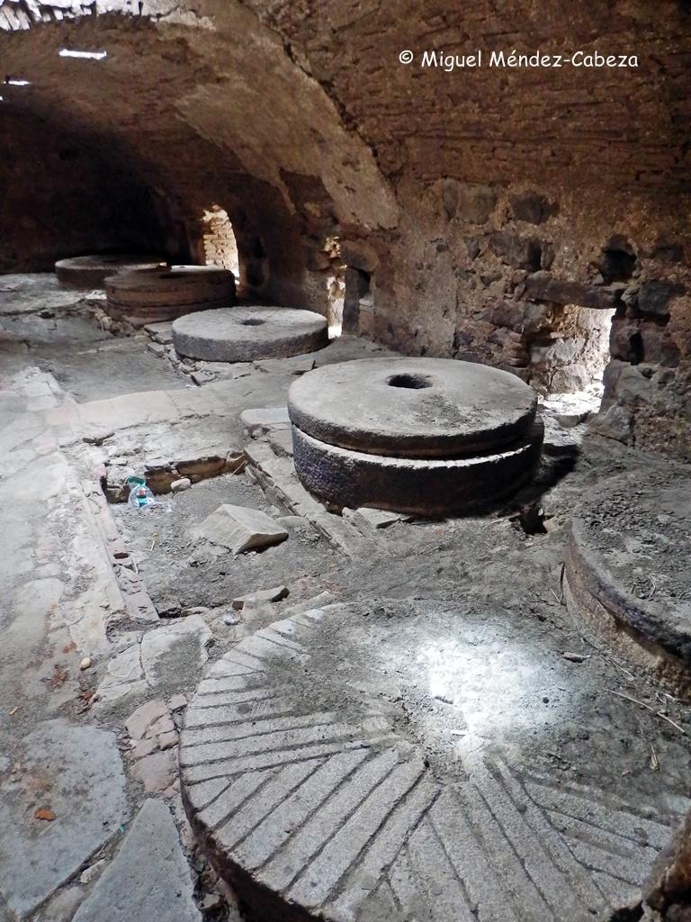 Interior de uno de los grandes molinos del Tajo. En primer plano el rayado de una piedra solera, detrás varios conjuntos de muela solera y volaera